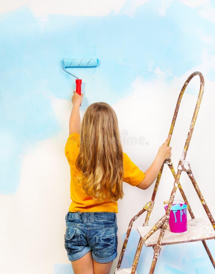 Lilla flickan målar vägganseendet på en stege royaltyfria foton