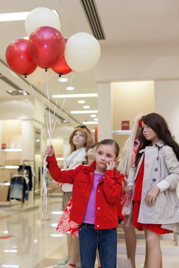 Lilla flickan med ballonger står med skyltdockor i lagret arkivfoto