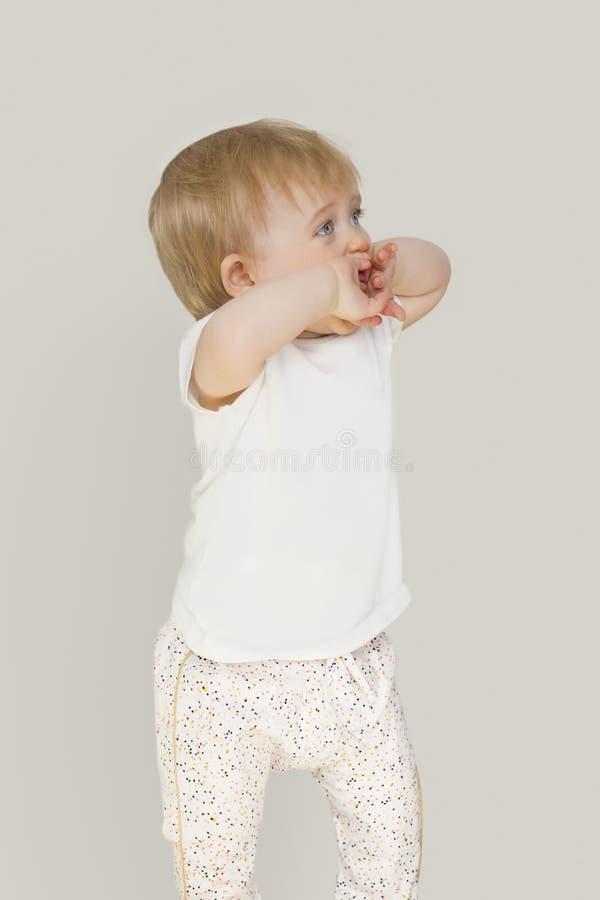 Lilla flickan med blåa ögon på en grå bakgrund täcker hans framsida med hans händer royaltyfri fotografi