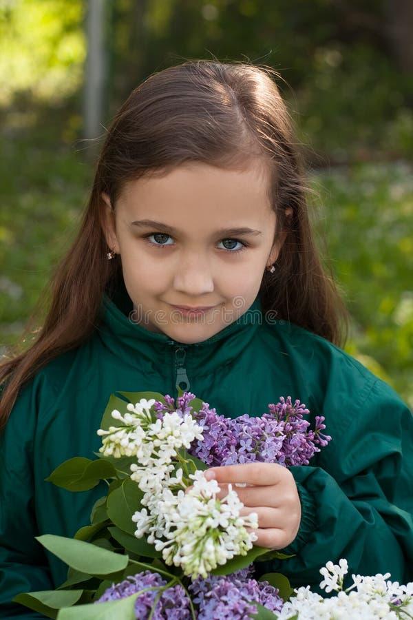 Lilla flickan med buketten av lilan blommar i trädgård royaltyfria bilder