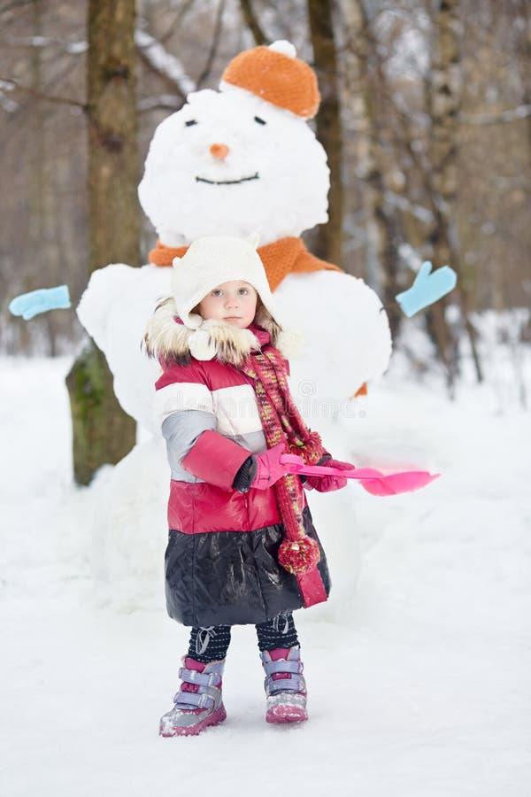 Lilla flickan med den röda plast- skyffeln står mot snögubben royaltyfria foton