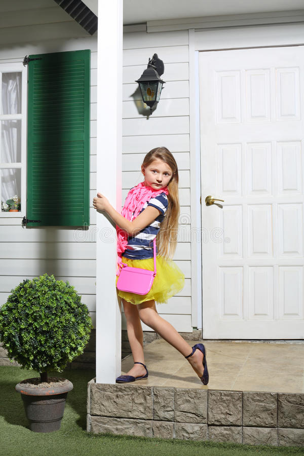 Lilla flickan med den rosa handväskan står på den vita farstubron arkivfoto