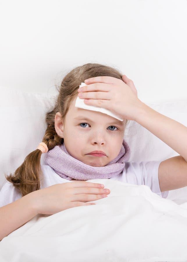Lilla flickan med en öm hals ligger i säng och applicerar en kompress till det öm huvudet royaltyfri foto