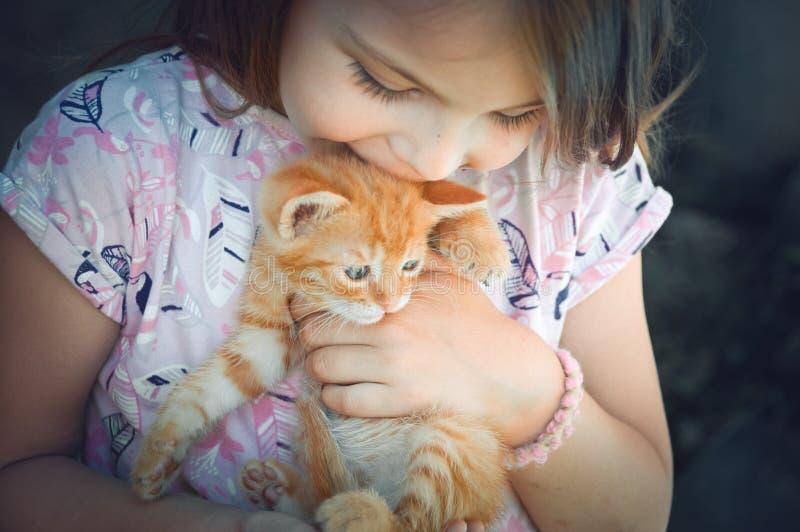 Lilla flickan med en röd kattunge i händer stänger sig upp BESTFRIENDS I arkivfoton