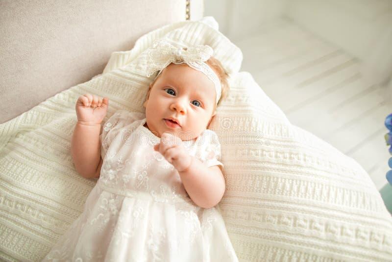 Lilla flickan med en vit pilbåge ligger på soffan, på en vit backg royaltyfri foto