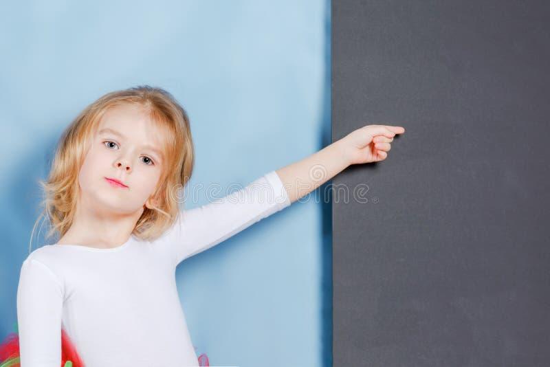 Lilla flickan med ett ganska hår visar ett finger på tomt utrymme på en svart bakgrund Härligt gulligt behandla som ett barn arkivfoton