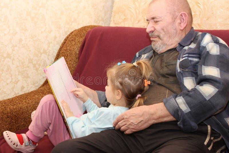 Lilla flickan med farfadern läste boken fotografering för bildbyråer