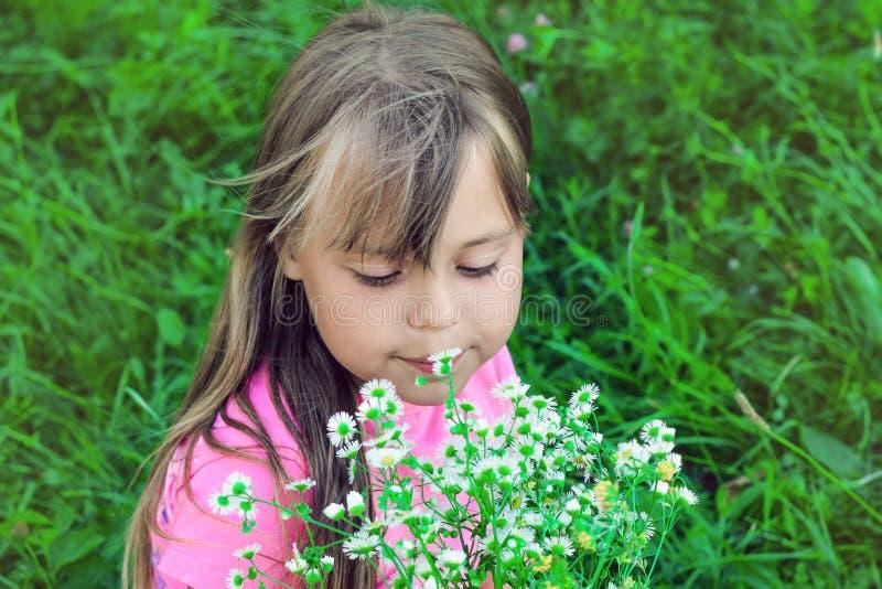 Lilla flickan med flödande hår sniffar vildblommor royaltyfri fotografi