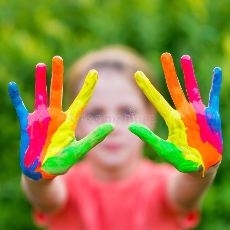 Lilla flickan med händer som målas i färgrika målarfärger som är klara för hand, skrivar ut royaltyfri foto