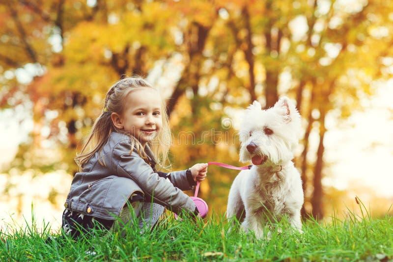 Lilla flickan med hunden i höst parkerar Gullig le flicka som har roligt, i att gå med hennes husdjur Lyckligt barn som utomhus v arkivbild