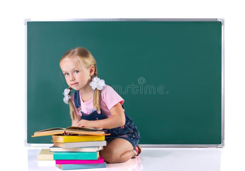 Lilla flickan med många bokar royaltyfri foto
