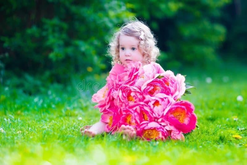 Lilla flickan med pionen blommar i trädgården arkivbild