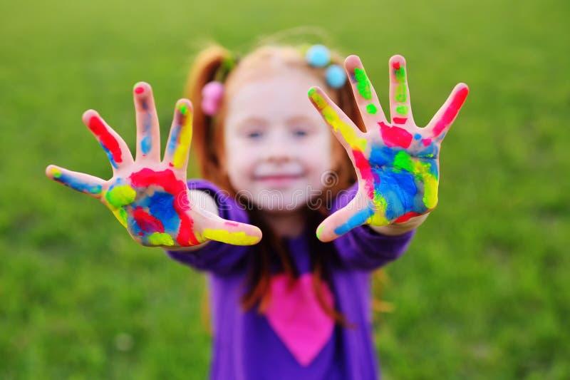 Lilla flickan med rött hår visar hennes händer som är smutsiga med mångfärgade målarfärger och leenden royaltyfri fotografi