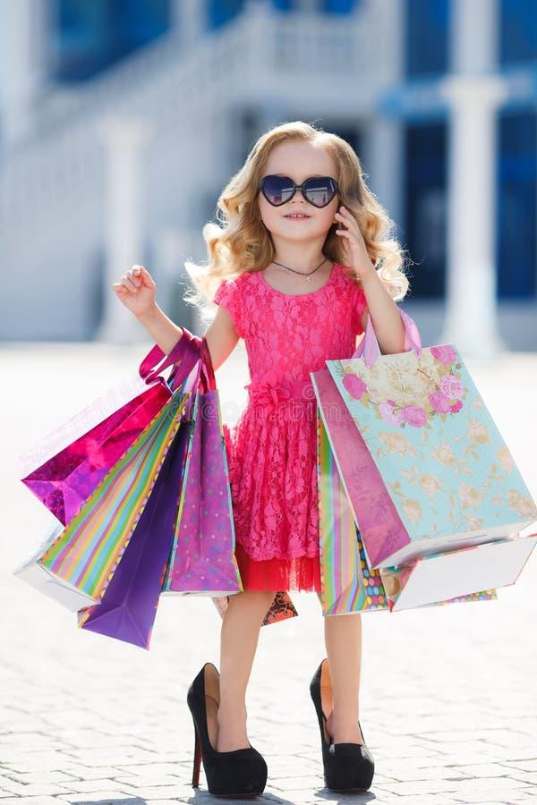 Lilla flickan med shoppingpåsar går till lagret arkivbilder