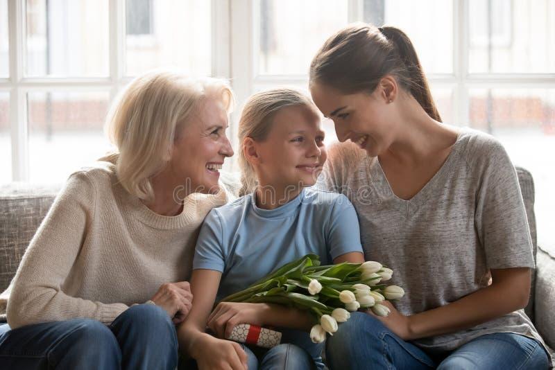 Lilla flickan mottog från moder och den farmorblommor och gåvan fotografering för bildbyråer