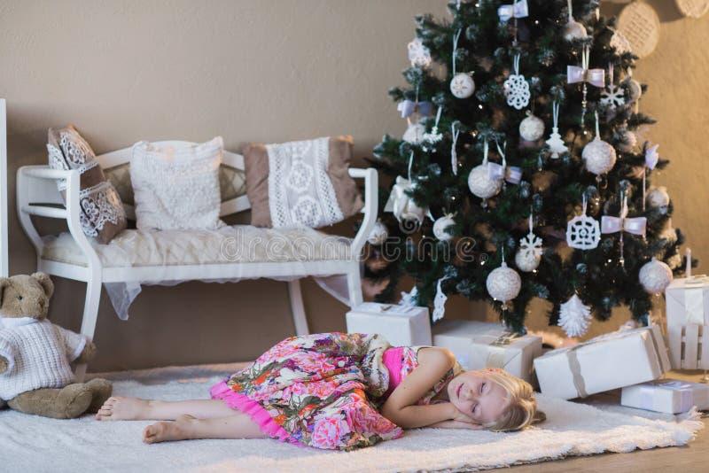 Lilla flickan nära julgranen hade väntande på jultomten för stupad sömn, förberedelsen för ferien som förpackar, askar, Christm royaltyfria foton