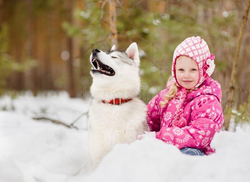 Lilla flickan och den hasky hunden i vinter parkerar tillsammans royaltyfri fotografi