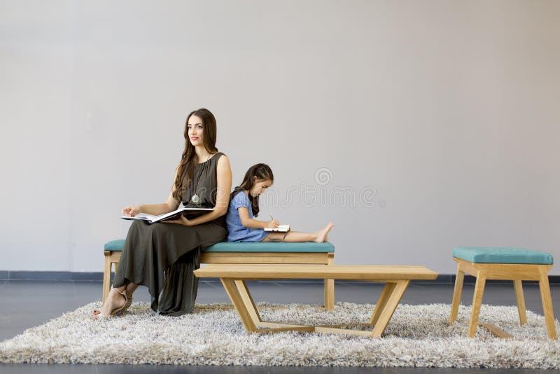 Lilla flickan och mamman sitter i läseböcker för ett rum arkivbilder