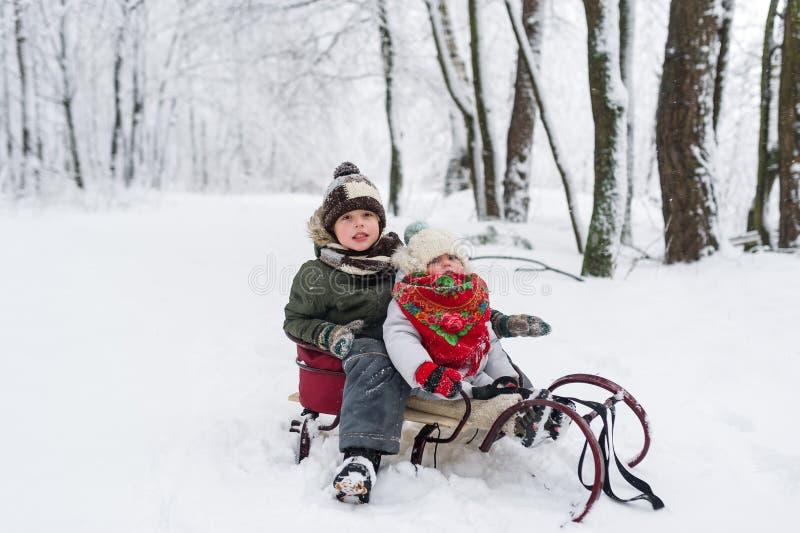 Lilla flickan och pojken tycker om en släderitt Sledding för barn Litet barnunge som rider en pulka Barnlek utomhus i snö royaltyfria bilder