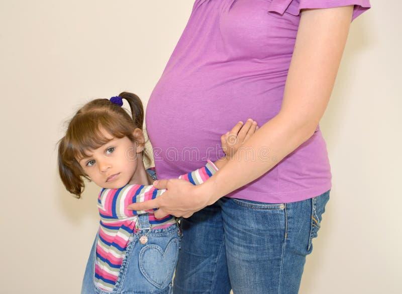 Lilla flickan omfamnar den gravida modern för händer royaltyfri foto