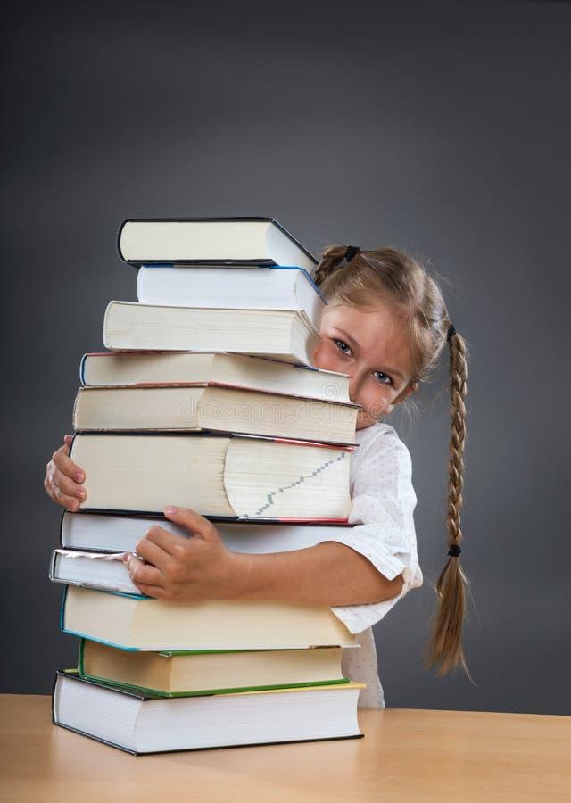 Lilla flickan omfamnar en hög av böcker royaltyfri bild