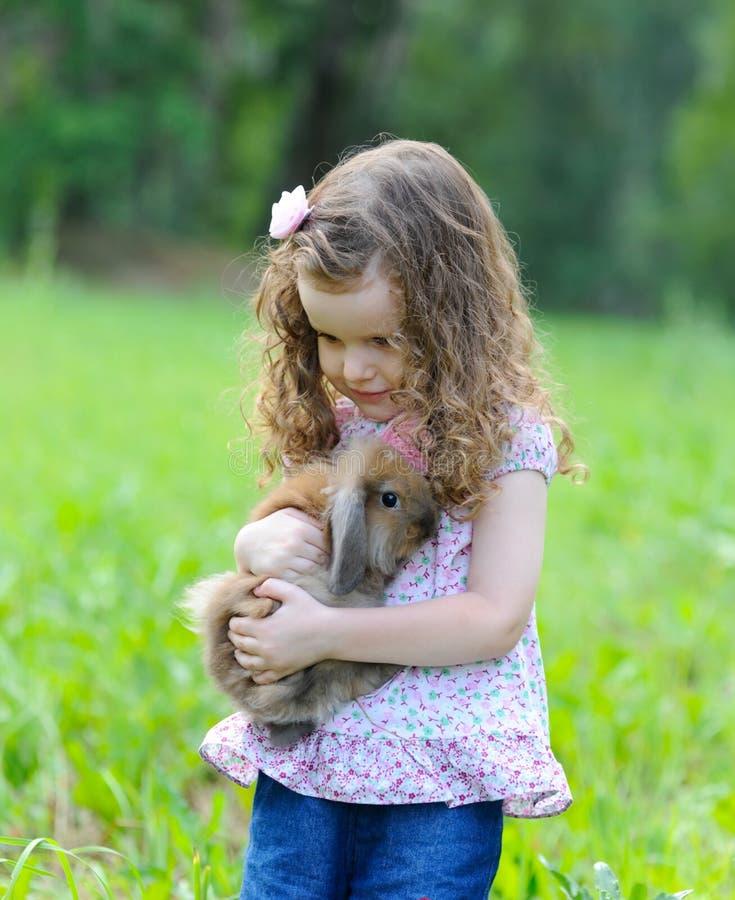 Lilla flickan omfamnar en kanin i en sommarträdgård arkivbilder