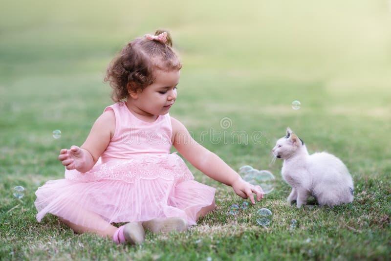 Lilla flickan på det gröna gräset som spelar med katten parkerar in royaltyfria bilder