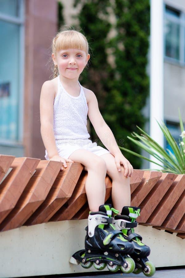 Lilla flickan på rullskridskor på parkerar royaltyfri foto
