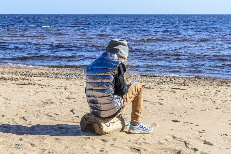 lilla flickan på stranden, mot bakgrunden av stenar, sand och härliga vågor av havet och oväsenet av vinden, sitter a royaltyfri foto