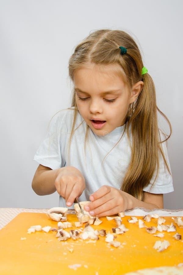 Lilla flickan på tabellen med arbetsamhetknivklipp plocka svamp royaltyfria bilder