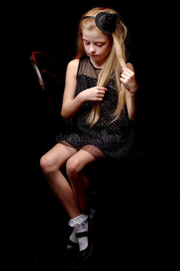 Lilla flickan rätar ut hennes hår i studion på en svart backgr fotografering för bildbyråer