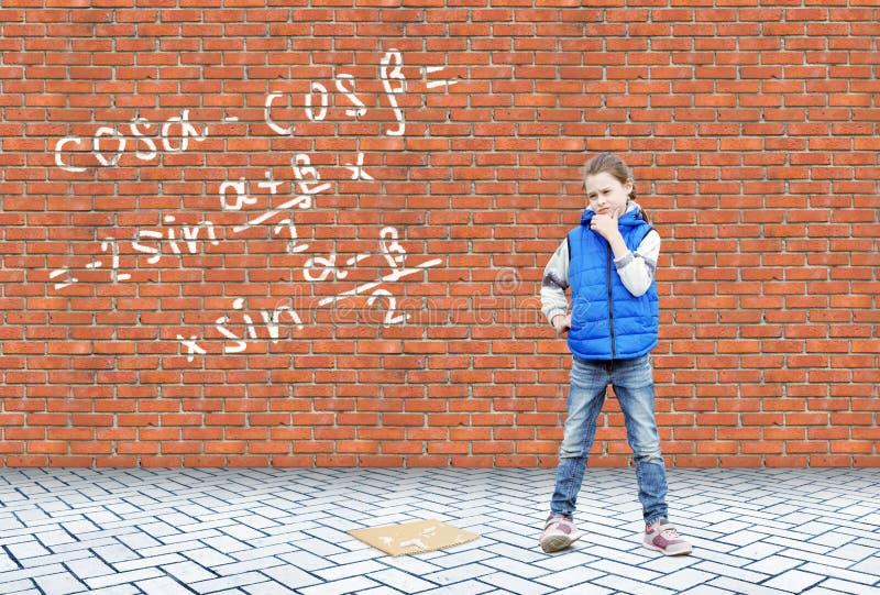 Lilla flickan reflekterar på matematiska formler som är skriftliga på en vägg royaltyfria foton