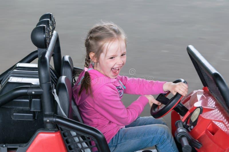 Lilla flickan rider på leksakelbilar i lekplatsen royaltyfria bilder