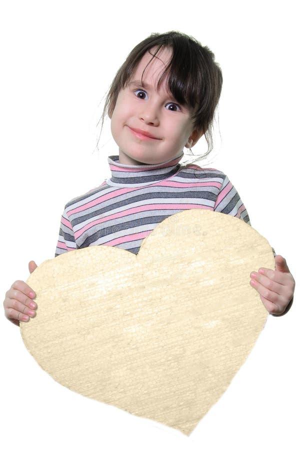 Lilla flickan rymmer en hjärta i hans händer royaltyfria foton