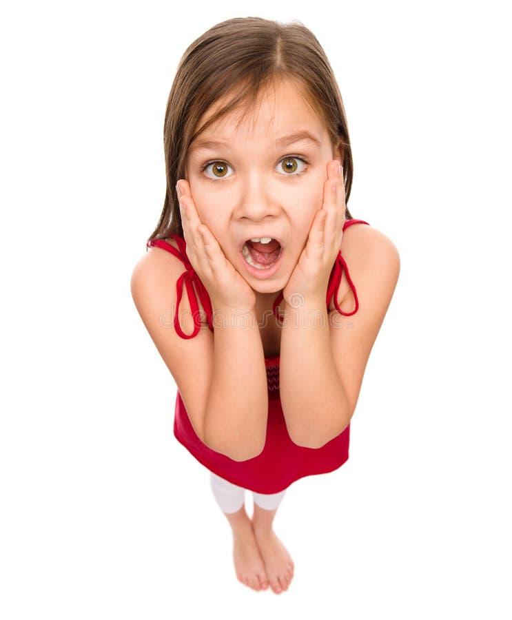 Lilla flickan rymmer hennes framsida i häpnad royaltyfri fotografi