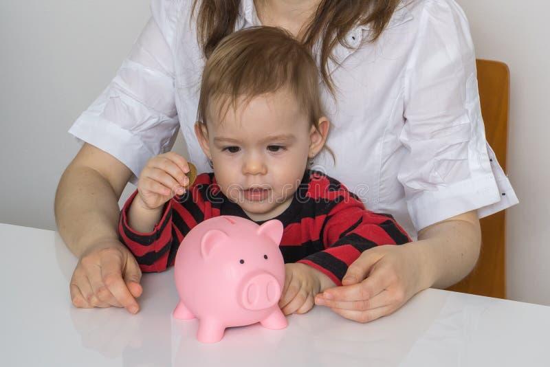 Lilla flickan sätter mynt i den piggy pengarbanken och samlar besparingar arkivbild