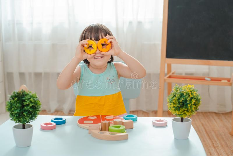Lilla flickan samlar en tr?om?lad pyramid S?kra naturliga tr?barns leksaker arkivbild