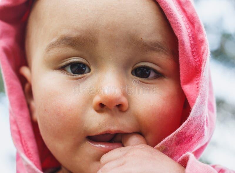 Lilla flickan satte fingret in i mun royaltyfria foton