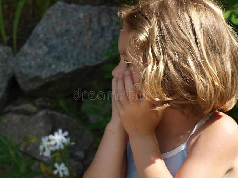 Lilla flickan ser bort med hennes händer över hennes mun royaltyfri fotografi