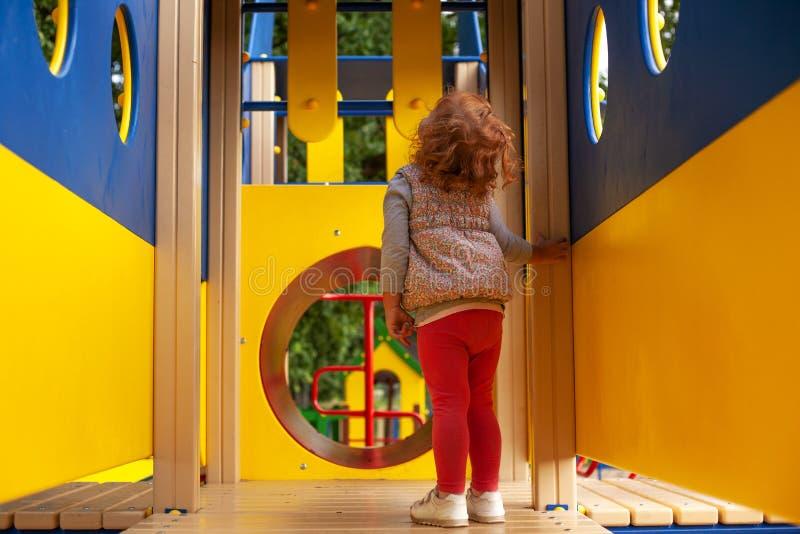 Lilla flickan ser himlen på en lekplats i nivån royaltyfria bilder