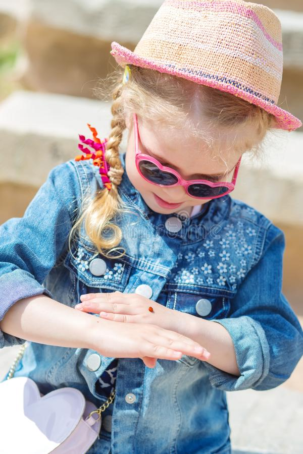 Lilla flickan ser nyckelpigan arkivbild