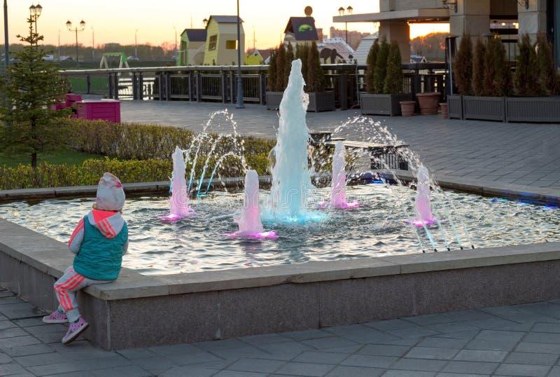 Lilla flickan ser springbrunnen på solnedgången på invallningen av staden royaltyfria bilder