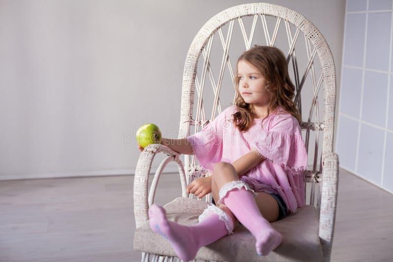 Lilla flickan sitter i en stol och en gröna Apple arkivfoto