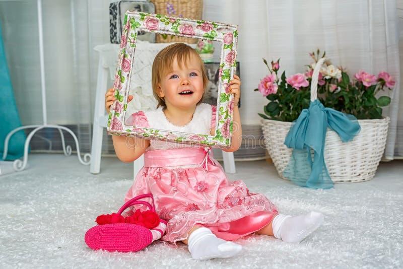 Lilla flickan sitter och ler royaltyfri fotografi