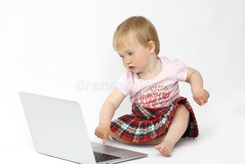 Lilla flickan sitter på datoren royaltyfri foto