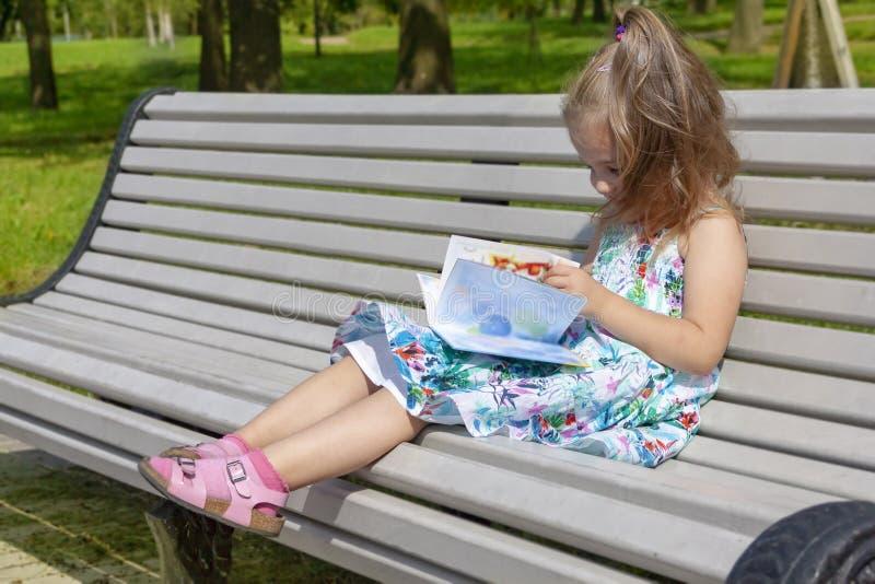 Lilla flickan sitter på en bänk i parkera och läser boken royaltyfria bilder