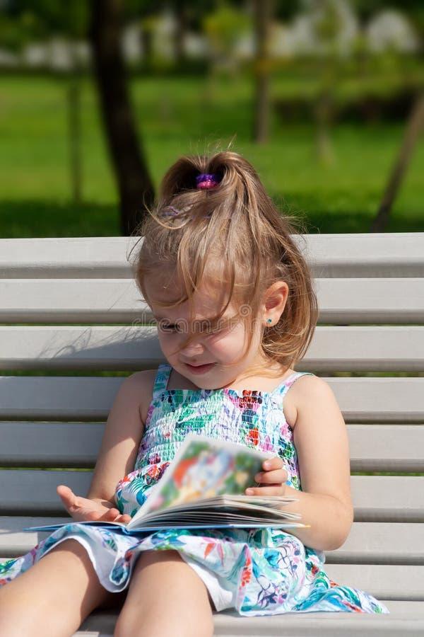 Lilla flickan sitter på en bänk i parkera och läser boken arkivfoto