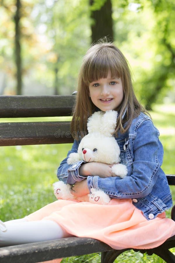 Lilla flickan sitter på en bänk och ett innehav i händerna av hennes favo royaltyfri bild