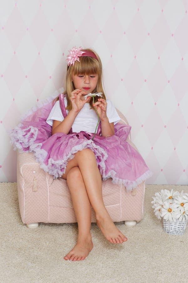 Lilla flickan sitter på en stol arkivbilder