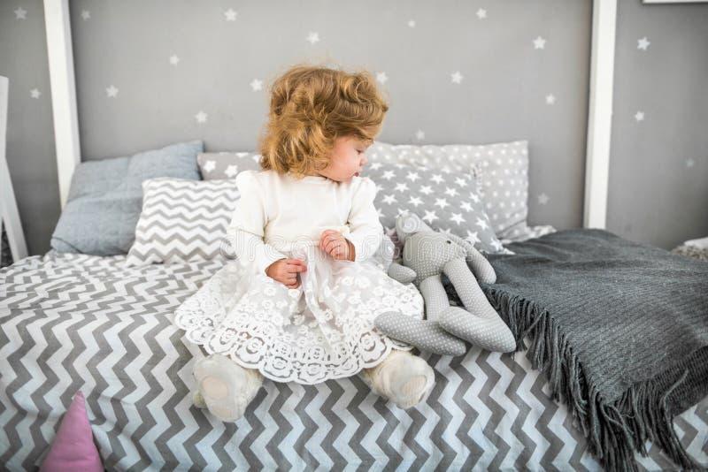 Lilla flickan sitter på sängen med hennes leksak fotografering för bildbyråer